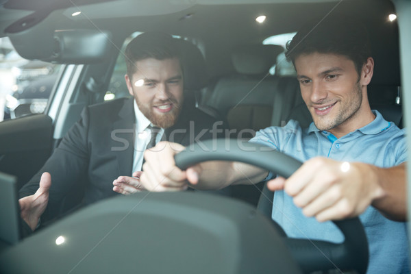 Professional young male dealer selling car to a customer Stock photo © deandrobot