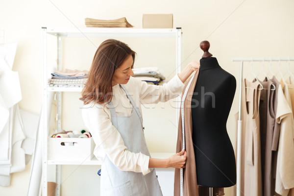 Seamstress measuring fabric on black dummy Stock photo © deandrobot
