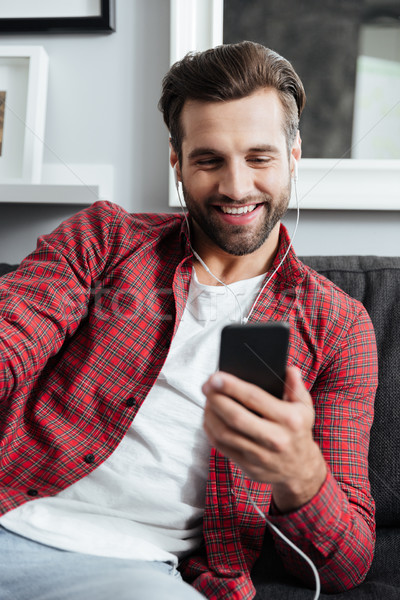 Young man using smartphone to make a videocall Stock photo © deandrobot