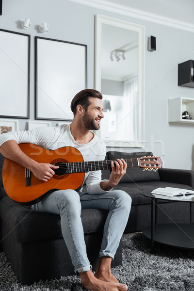 Happy man sitting on sofa playing on guitar. Stock photo © deandrobot