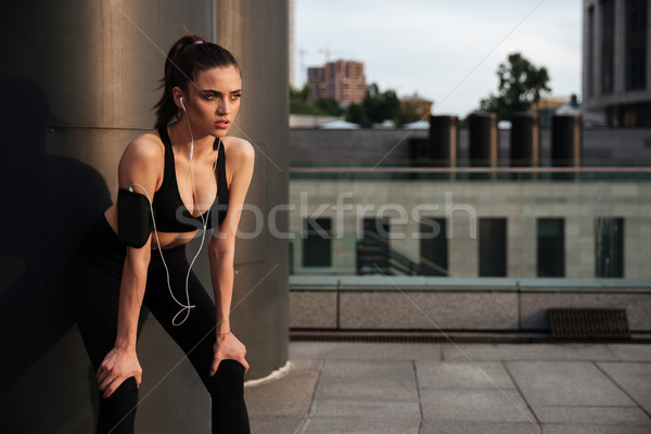 Stock photo: Beautiful young sports woman standing with earphones
