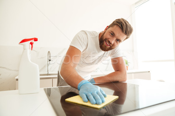 Happy casual bearded man wipes a stove on kitchen Stock photo © deandrobot