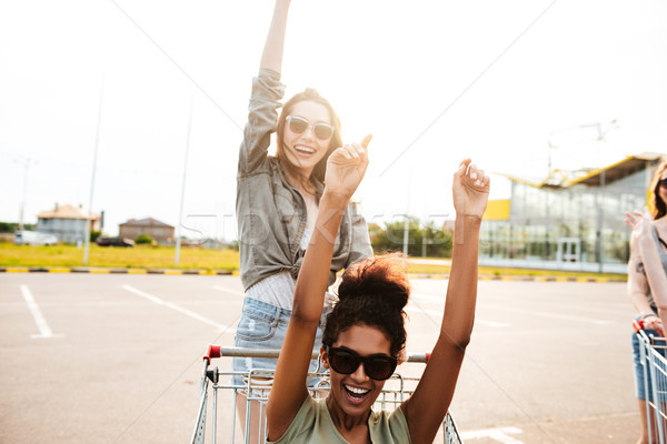 Young amazing women friends have fun with shopping trolleys. Stock photo © deandrobot