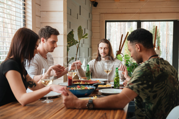 Side view picture of a group of friends praying over dinner table Stock photo © deandrobot