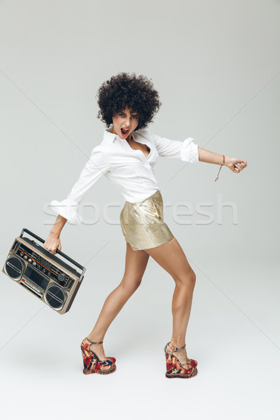 Emotional retro woman dressed in shirt holding boombox. Stock photo © deandrobot