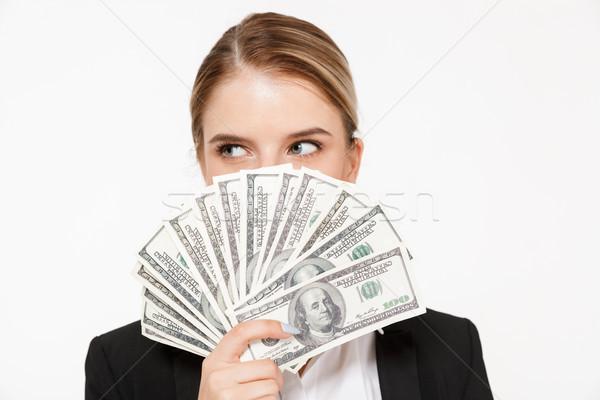 Csinos szőke nő üzletasszony rejtőzködik pénz másfelé néz Stock fotó © deandrobot