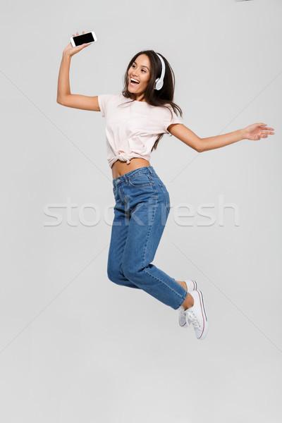 Portrait of a joyful satisfied asian woman in headphones Stock photo © deandrobot