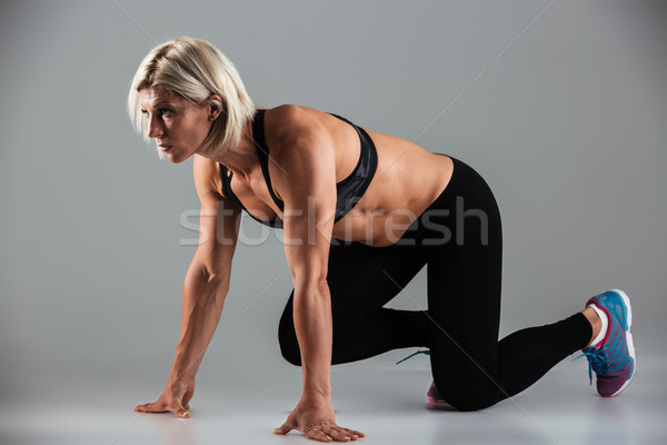 Full length portrait of a concentrated musculal fit sportswoman Stock photo © deandrobot