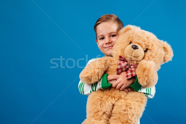 Smiling young boy holding teddy bear and looking at camera Stock photo © deandrobot