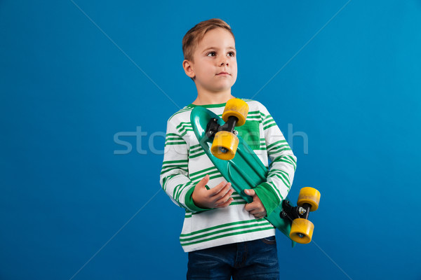 Picture of Young boy holding skateboard and looking aside Stock photo © deandrobot
