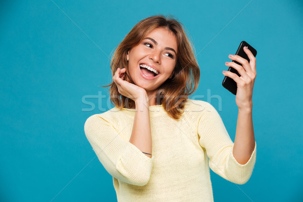 Laughing woman in sweater making selfie on smartphone Stock photo © deandrobot