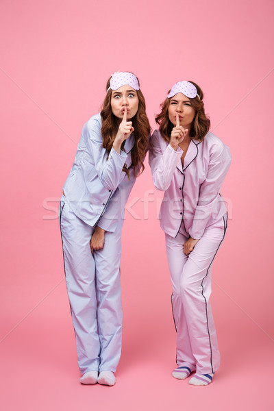 Funny displeased two women friends in pajamas showing silence gesture. Stock photo © deandrobot