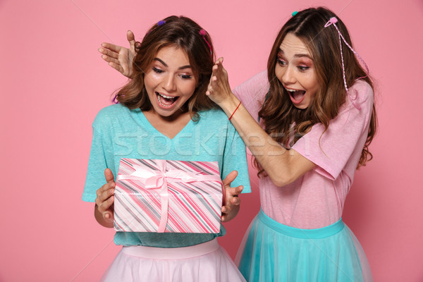 Close-up photo of happy brunette woman giving gift box to her fr Stock photo © deandrobot