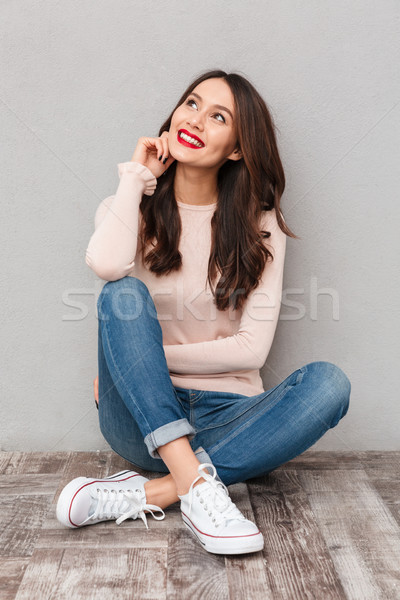 Picture of beautiful woman with makeup in jeans sitting with leg Stock photo © deandrobot