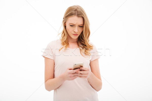 Displeased young woman using mobile phone. Stock photo © deandrobot
