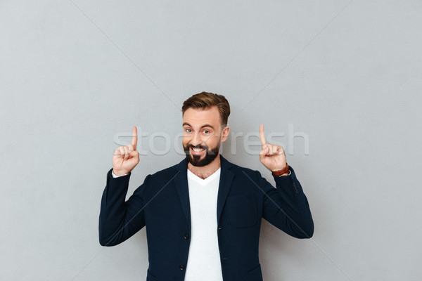 Happy bearded man in business clothes pointing up Stock photo © deandrobot
