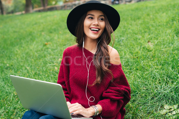 Stock photo: Portrait of a cheerful asian girl in earphones using laptop
