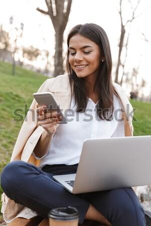 Genç başarılı iş kadını siyah takım elbise konuşma cep telefonu Stok fotoğraf © deandrobot
