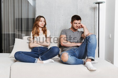 Displeased young loving couple sitting on sofa quarrel. Stock photo © deandrobot