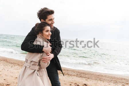 Smiling young man carrying his girlfriend on his back Stock photo © deandrobot