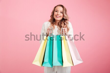 Happy young pretty woman shopaholic holding shopping bags. Stock photo © deandrobot