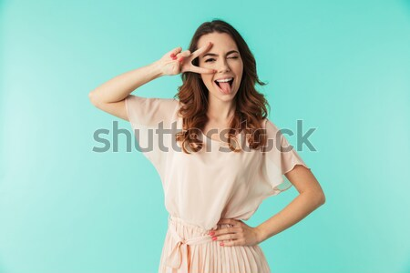 Photo of young fancy woman 20s wearing pink dress smiling and sh Stock photo © deandrobot
