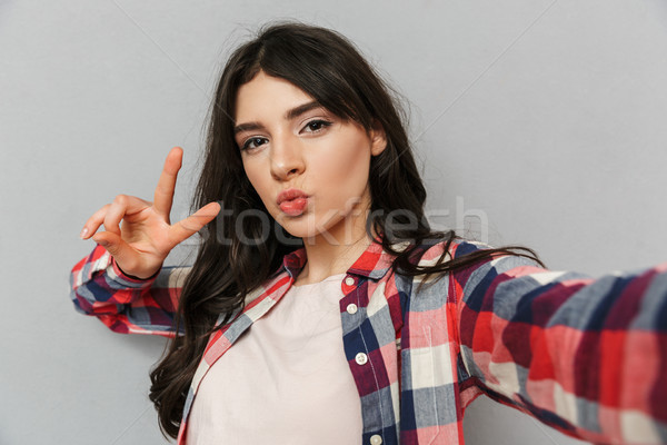 Cute beautiful young lady make selfie looking camera make peace gesture. Stock photo © deandrobot