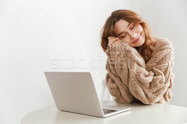 Image of relaxed woman 20s with closed eyes sitting at table in  Stock photo © deandrobot