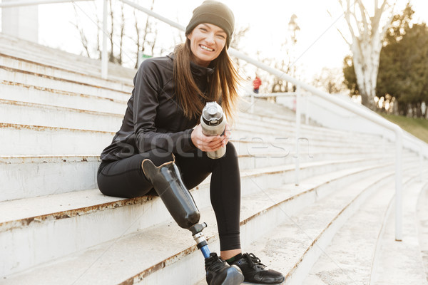 Strong willed handicapped woman in black tracksuit with prosthet Stock photo © deandrobot