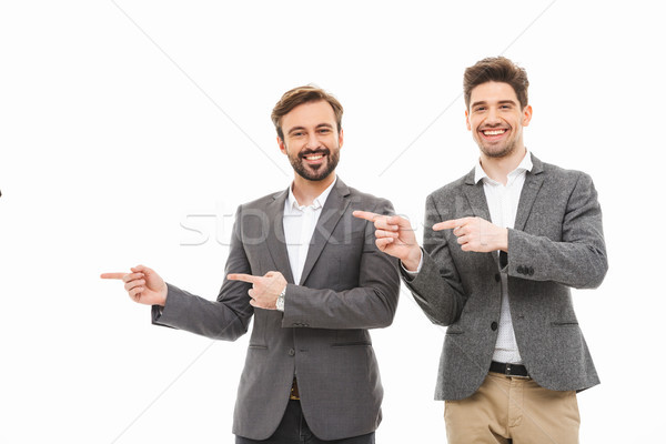 Portrait of a two satisfied business men pointing away Stock photo © deandrobot