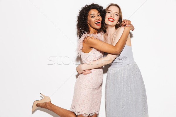 Portrait of two happy well dressed women hugging Stock photo © deandrobot