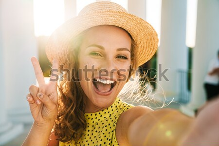 Photo of positive caucasian woman 20s in summer straw hat smilin Stock photo © deandrobot