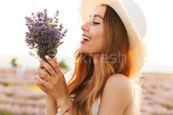 Beautiful young girl in straw hat holding lavender bouquet Stock photo © deandrobot
