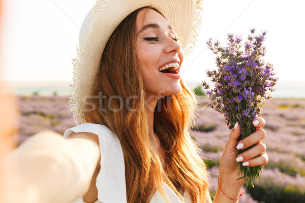 Positive young girl in straw hat holding lavender bouquet Stock photo © deandrobot