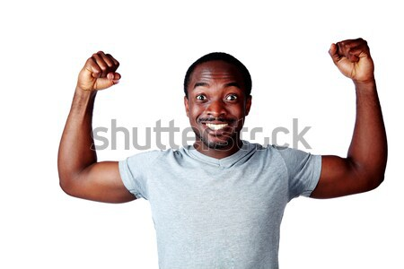 Portrait of african man with raised hands over white background Stock photo © deandrobot