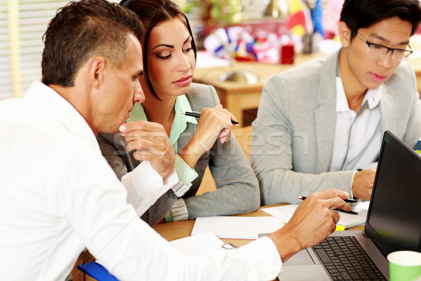 Business people working around table in office Stock photo © deandrobot