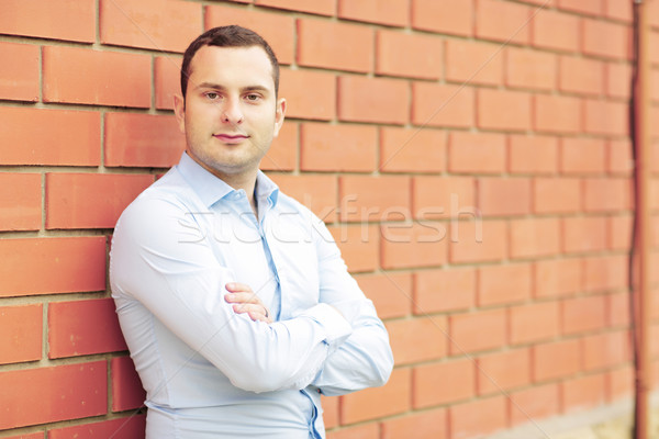 Happy businessman against brick wall Stock photo © deandrobot