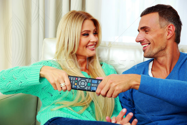Happy couple bickering to change tv channel on remote control Stock photo © deandrobot