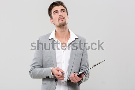 Portrait of a pensive asian man with arms folded isolated on a white background Stock photo © deandrobot