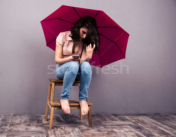 Woman sitting on the chair with smartphone and umbrella Stock photo © deandrobot