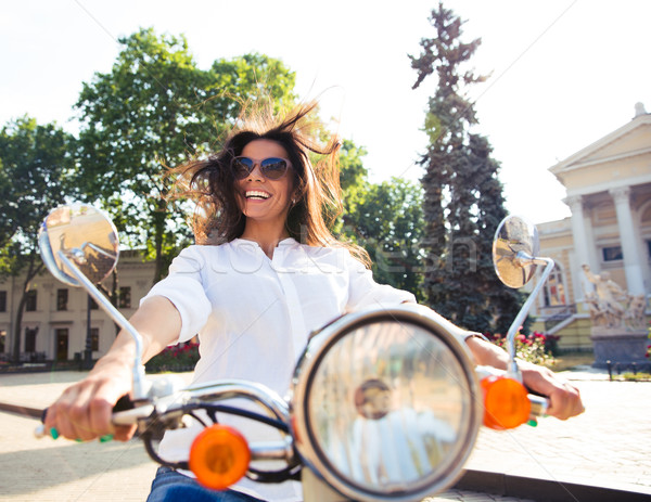 Cheerful cute woman driving scooter Stock photo © deandrobot