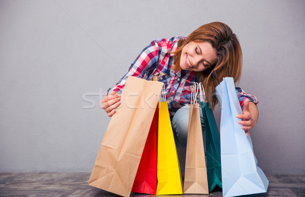 Happy woman sitting with shopping bags Stock photo © deandrobot