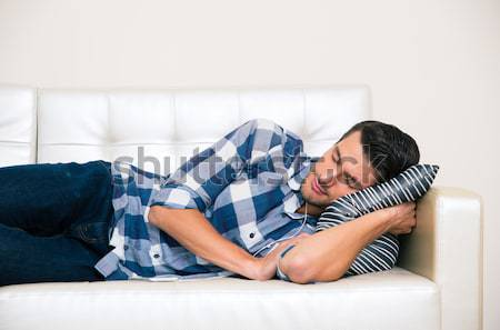 Man sleeping in cloth and headphones on the sofa  Stock photo © deandrobot