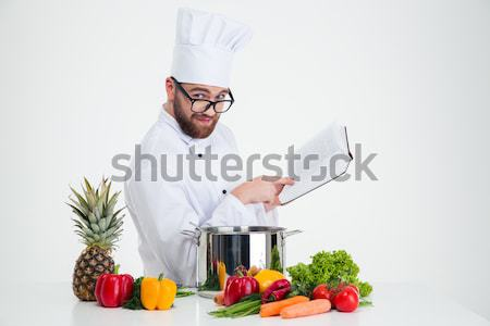 Male chef cook reading recipe book while preparing food Stock photo © deandrobot