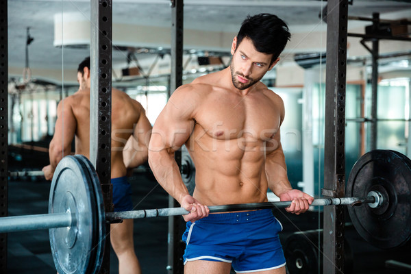 Muscular man workout with barbell Stock photo © deandrobot
