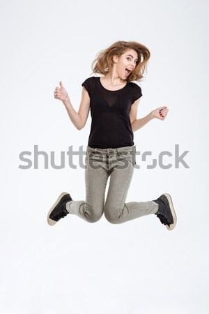 Portrait of a cheerful woman jumping  Stock photo © deandrobot