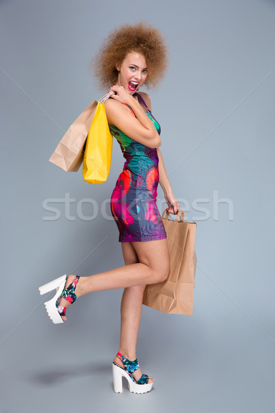 Full length portrait of happy curly woman with shopping bags  Stock photo © deandrobot