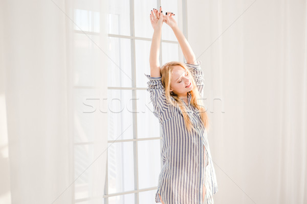 Smiling sleepy woman waking up and stretching near window Stock photo © deandrobot