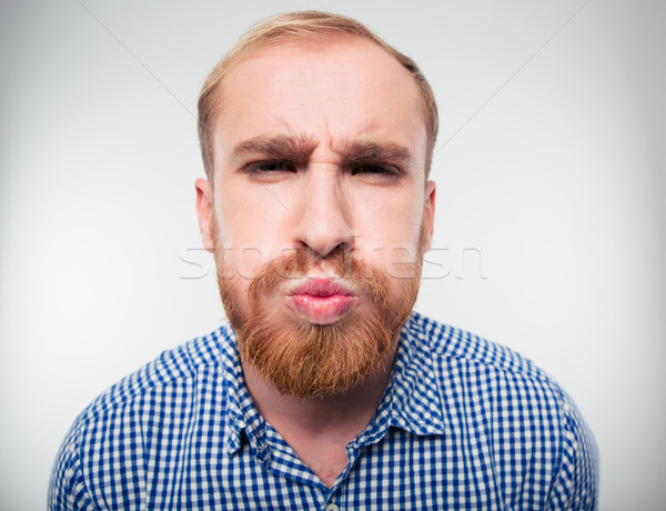 Funny young man inflate his cheeks Stock photo © deandrobot