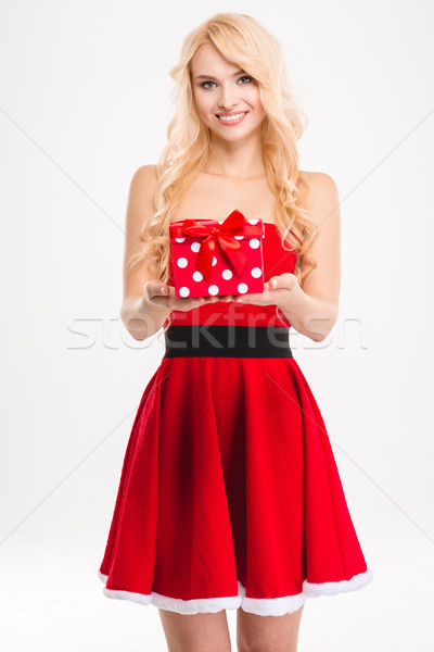 Cheerful blonde girl in red santa claus costume holding present  Stock photo © deandrobot